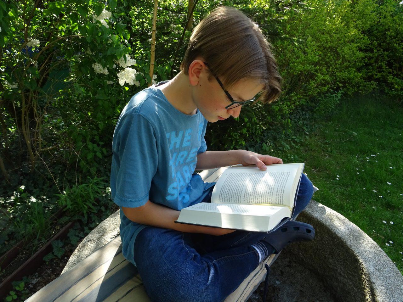 Daniel sitzt auf dem Brunnen und liest ein Buch.